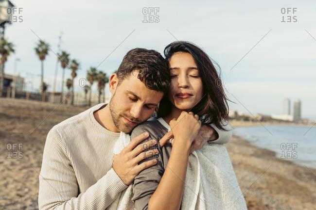 Boyfriend embracing girlfriend against sky at beach