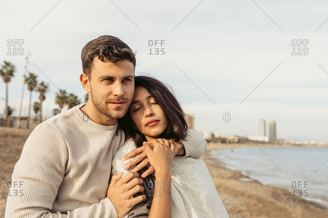 Boyfriend embracing girlfriend while standing against sky at beach