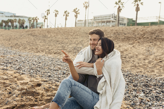 Smiling girlfriend pointing while embracing boyfriend at beach