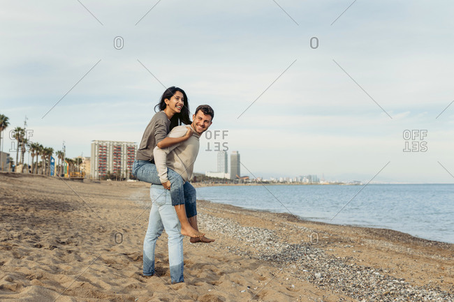 Young man giving piggyback ride to woman against sky at beach
