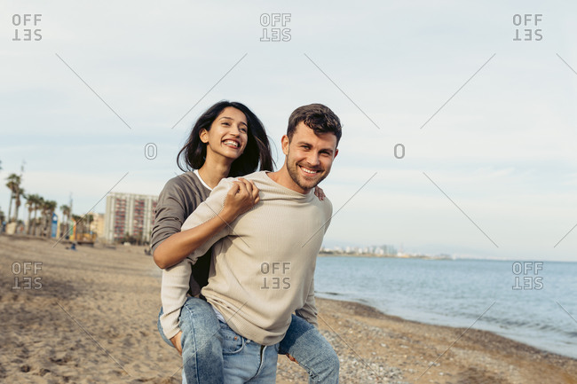 Smiling boyfriend while giving piggyback ride to girlfriend at beach