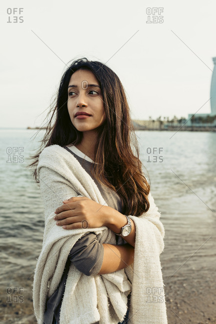 Contemplating woman with arms crossed looking away at beach