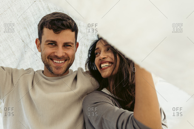Young couple smiling while standing below shawl outdoors