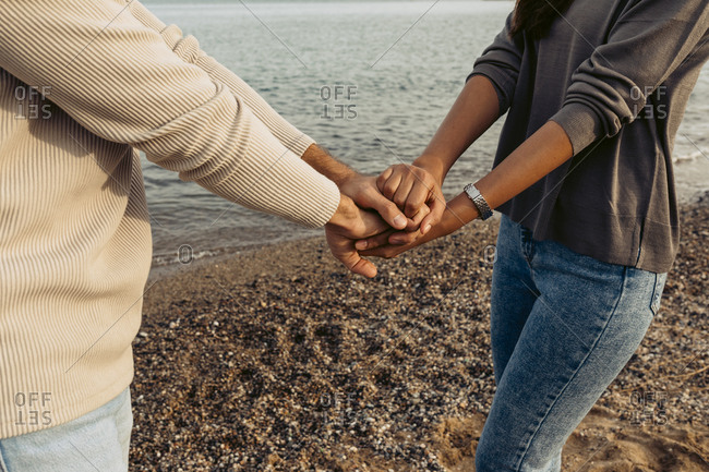 Girlfriend and boyfriend stacking hands while standing at beach