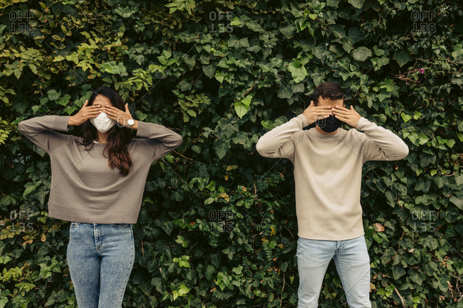 Young couple covering eyes with hands against plants in park during COVID-19