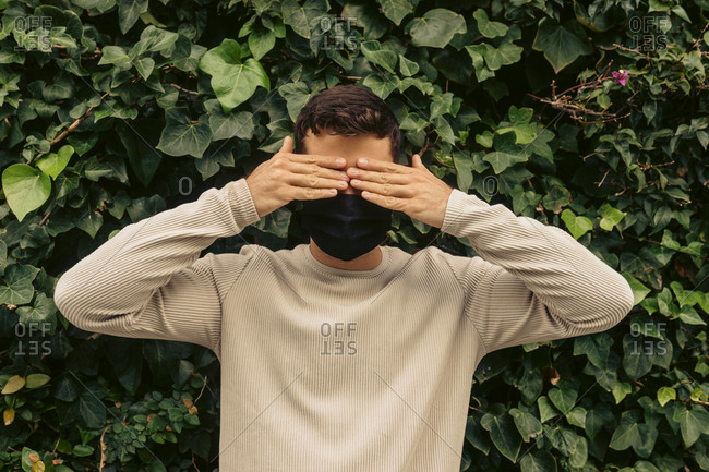 Young man covering eyes with hands against leaves in park during pandemic