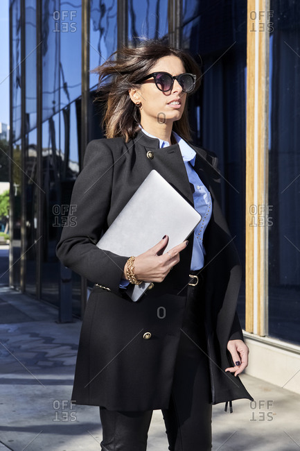 Businesswoman standing with laptop by financial district on sunny day