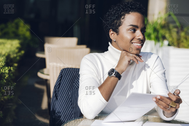 Smiling businesswoman looking away while holding menu at restaurant during sunny day