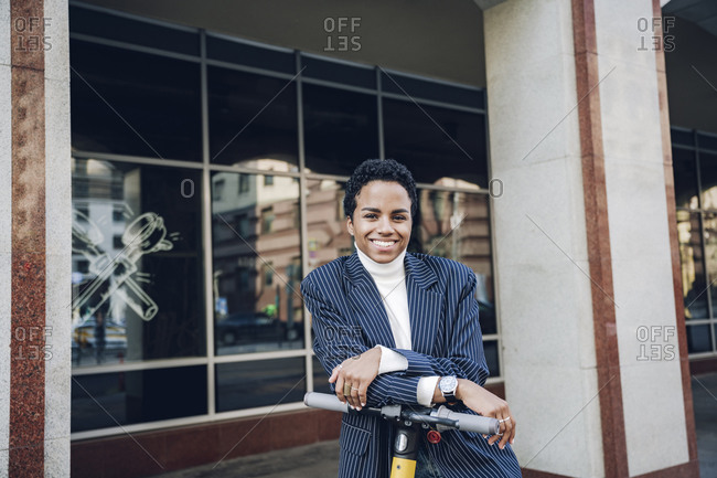 Smiling businesswoman with electric push scooter in city