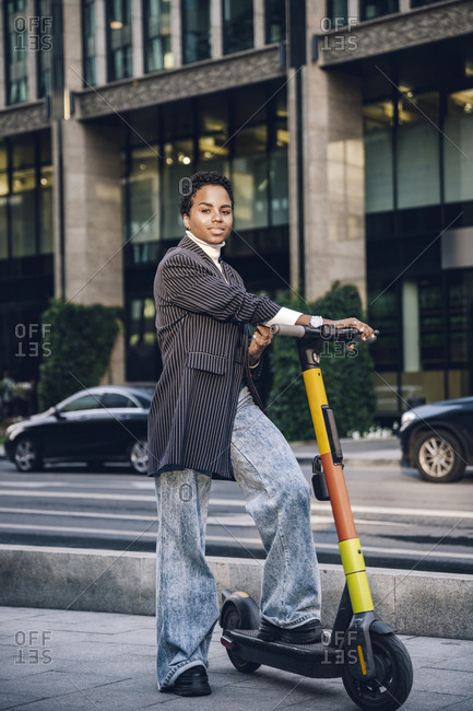 Confident businesswoman with electric push scooter on street in city