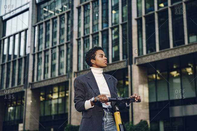 Thoughtful young businesswoman with electric push scooter against modern building in city