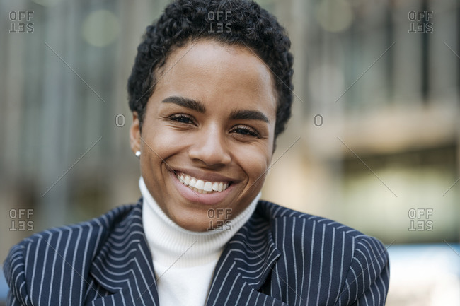Smiling young businesswoman with short hair wearing blazer
