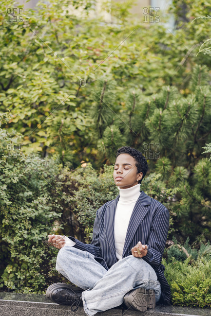 Young businesswoman meditating while sitting on retaining wall against plants