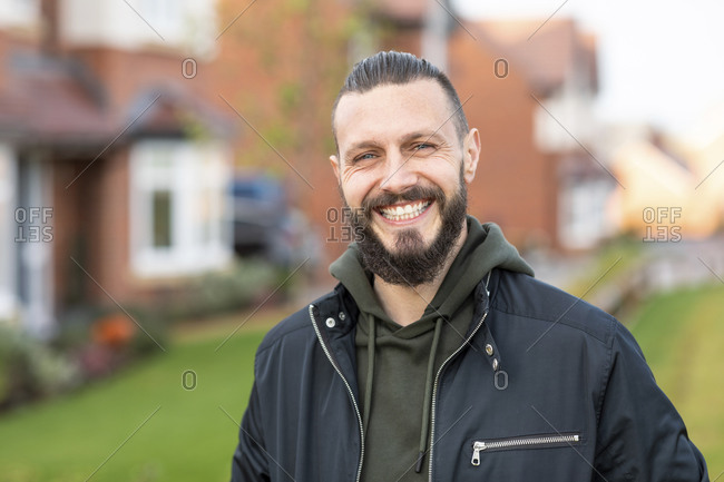 Happy bearded man standing in front yard