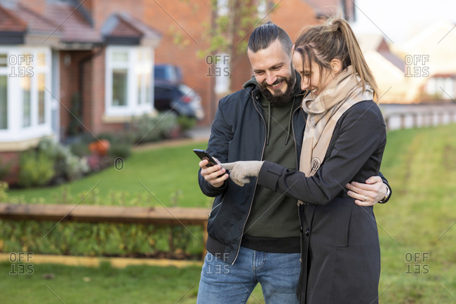 Happy couple looking at smart phone while standing in front yard
