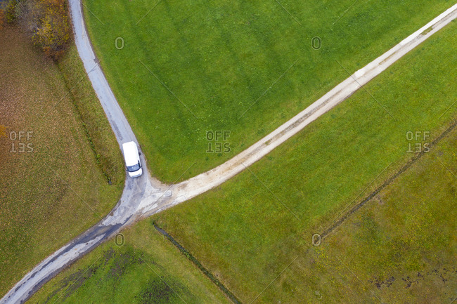 Drone view of van passing countryside crossroad in autumn