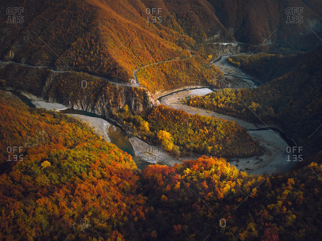 Aerial view of the Trebbia river canyon in Autumn and a colorful trees foliage on the hills near Brugnello, Emilia-Romagna, Italy.