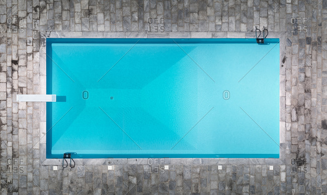 Aerial view of a resort's beautiful swimming pool with diving board and turquoise water in Monticello, Lombardy, Italy.