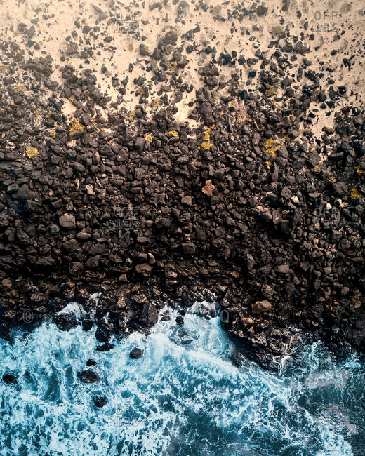 Aerial view of a rocky beach made of lava and sand surrounded by rough waters in Famara, Lanzarote, Spain.