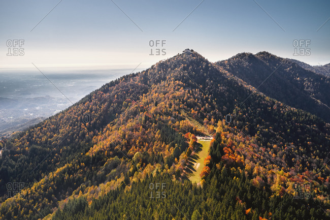 Aerial view of many colorful trees in Autumn on the gentle hills near Trivero, Piedmont, Italy.