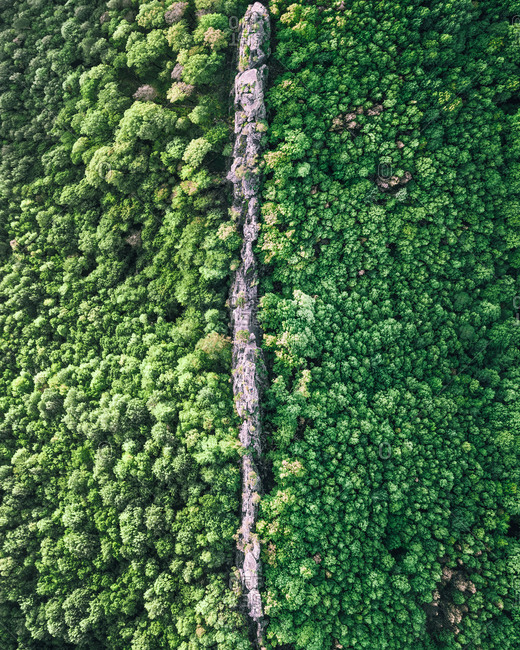 Aerial view of a narrow ridge of rocks with the little people on top in the middle of the forest, Monastery rocks, Gelendzhik, Russia