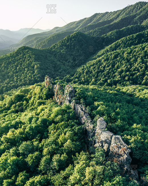 Aerial view of a narrow ridge of rocks with the little people on top in the middle of the green waves of forest, Monastery rocks, Gelendzhik, Russia