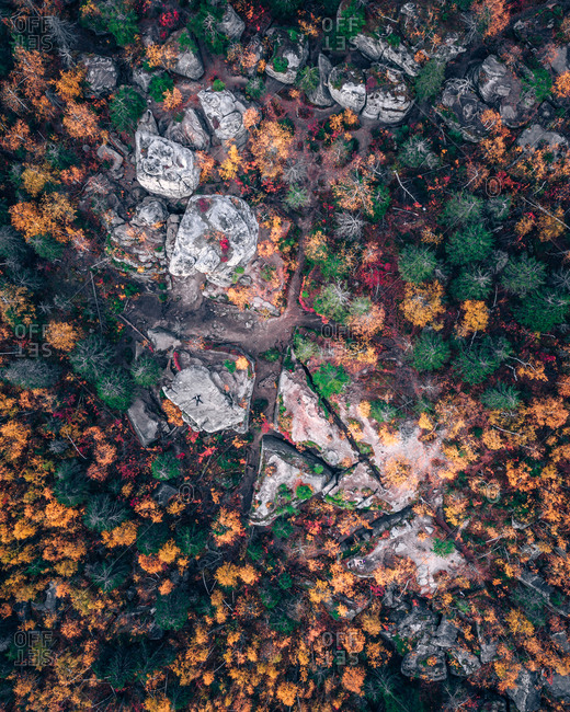 Aerial view of lying down man on the top of big stones in the autumn forest from above, Usva, Perm Krai, Russia