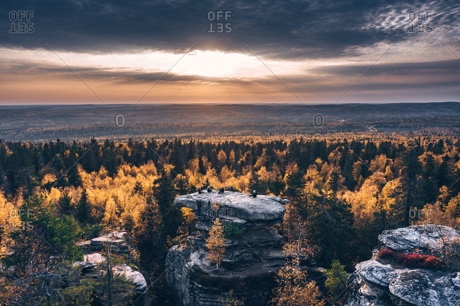 Aerial view of big stone in the autumn forest in time of the sunset with sitting people on the top, Usva, Perm Krai, Russia