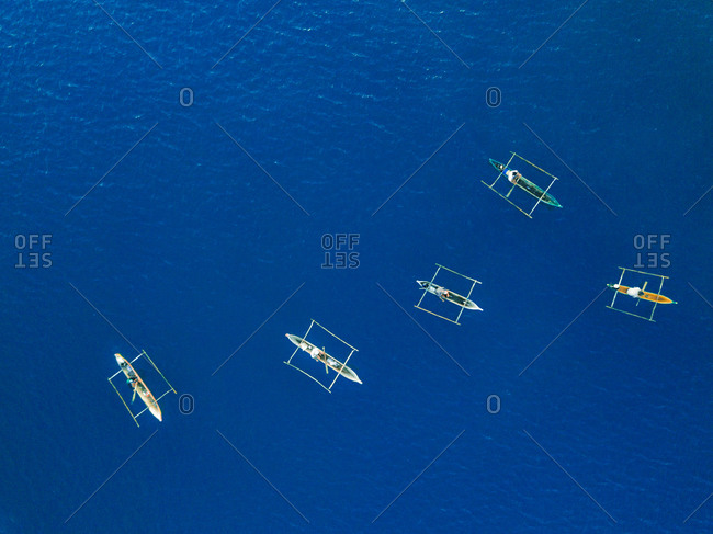 Aerial view of fishermen fishing using pirogue boats on deep blue ocean waters during sunrise in Dili, Timor-Leste