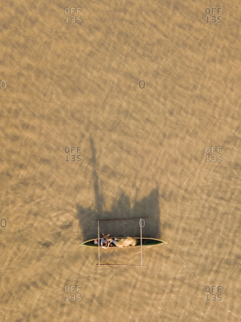 Aerial view of a fisherman and his mirror shadow fishing using a pirogue boat on brownish muddy waters during sunrise in Dili, Timor-Leste