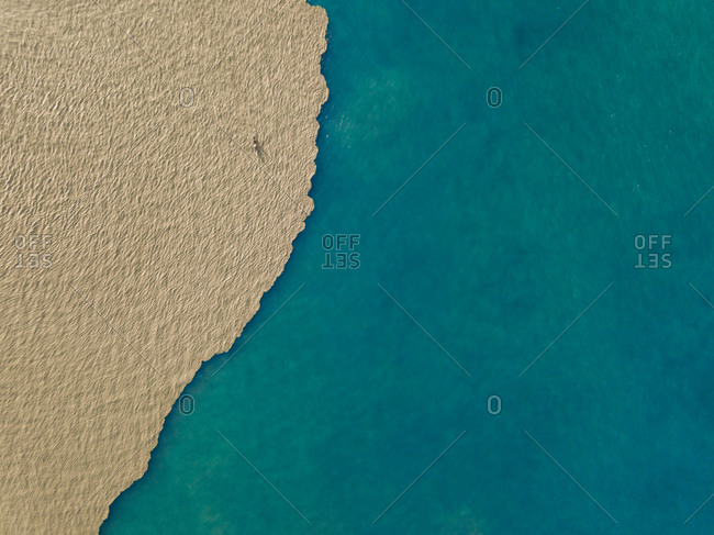 Aerial view of a fisherman fishing in the mouth of the muddy Comoro river with the green coral reef ocean in Dili, Timor-Leste