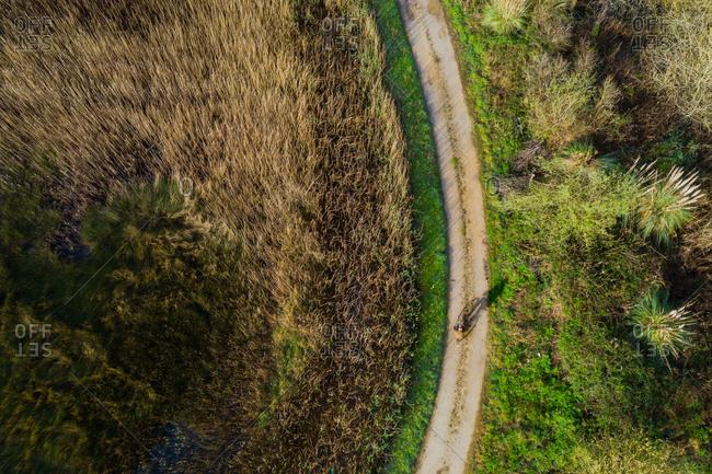 Aerial view of a old man riding a bicycle in a marshland part of estuary of river Vouga, in Ria de Aveiro, Bioria, Salreu, Estarrega, Aveiro, Portugal