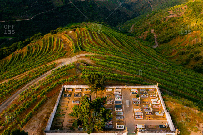 May 23, 2020: Aerial view of a cemetery above the vineyards terraces used for production of Port Wine, in Desejosa, Douro Valley, Portugal