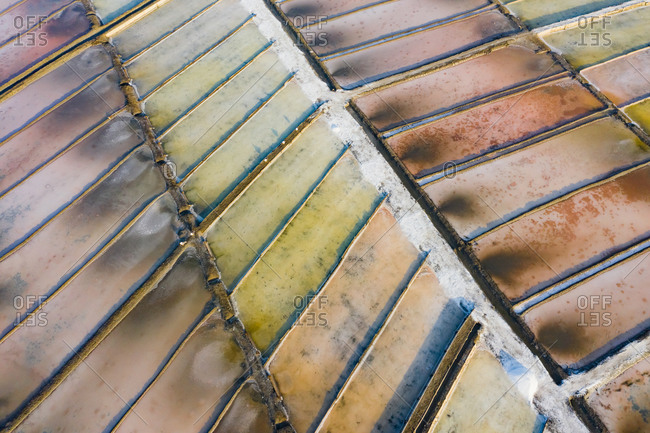 Aerial view of the patterns and colors of salt evaporation ponds during sunrise time in Aveiro, Portugal