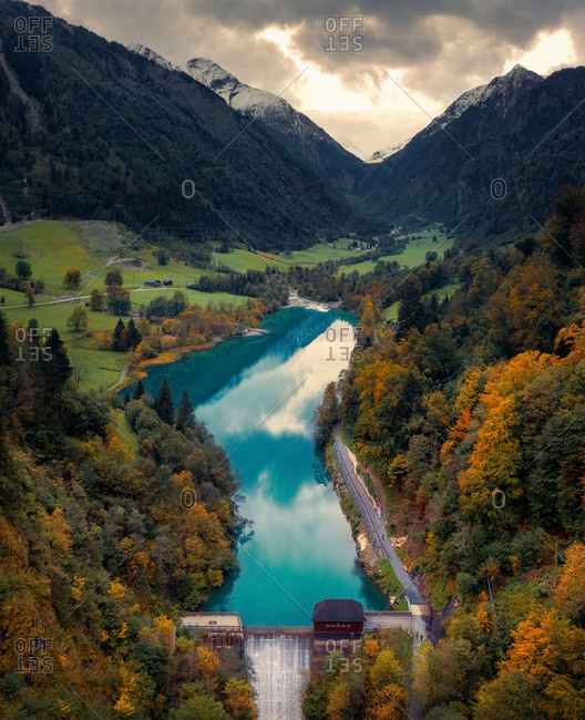 Aerial view of reservoir Klamsee, with turquoise water and little waterfall, Kaprun, Salzburg, Austria