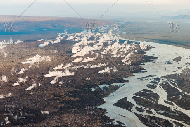 Aerial view of steam ascending from hot lava slowly flowing into the river Jokulsa a Fjollum during volcanic eruption of Holuhraun in September 2014, highlands of Iceland