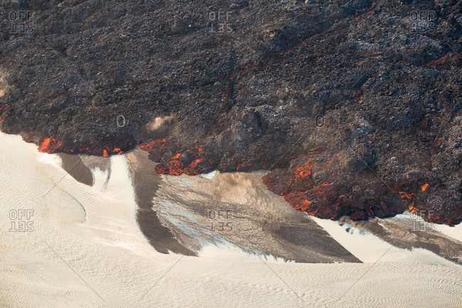 Aerial view of hot lava slowly flowing into the river Jokulsa a Fjollum during volcanic eruption of Holuhraun in September 2014, highlands of Iceland