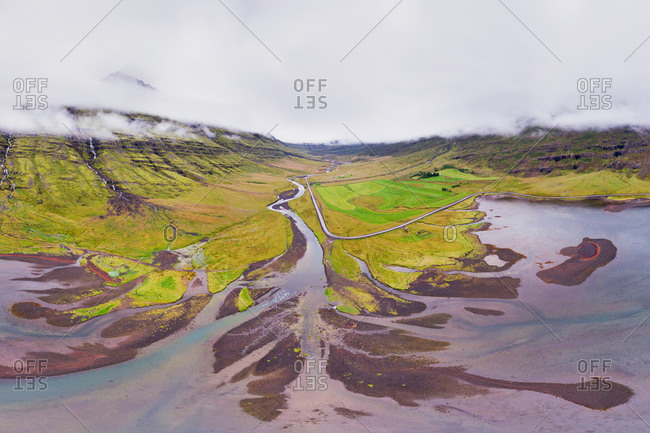 Aerial view of sandbars, a river and farmland at the end of a fjord with low clouds around the mountains, Mjoifjordur, Eastfjords of Iceland