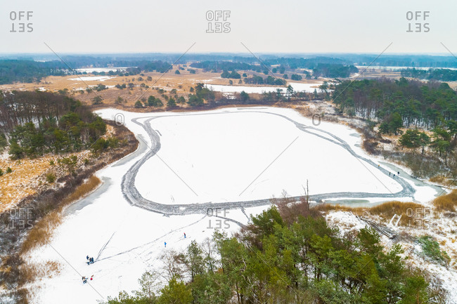 Aerial view of skaters on a frozen lake in a forest, Buurserzand, Twente, Overijssel, Netherlands