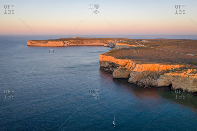 Aerial view of sailboat near cliffs in Atlantic ocean, Sagres, Portugal