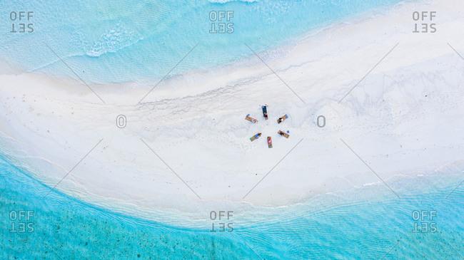 Aerial view of a group of women, doing sunrise yoga at a sandbank, Baa Atoll, Maldives.