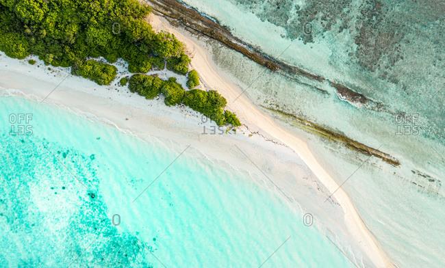 Aerial view of the top of Vashafaru Island, Maldives, Haa Alif Atoll with a sandbank and reef.