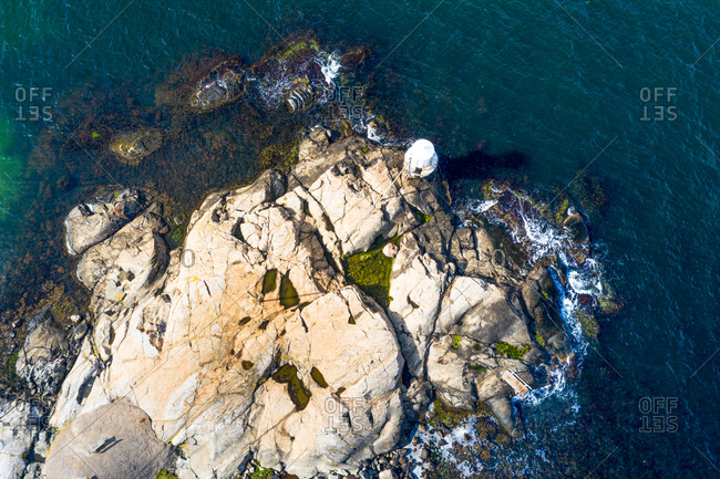Aerial view of a lighthouse on the rocks with breaking waves, Gothenburg Archipelago, Sweden.