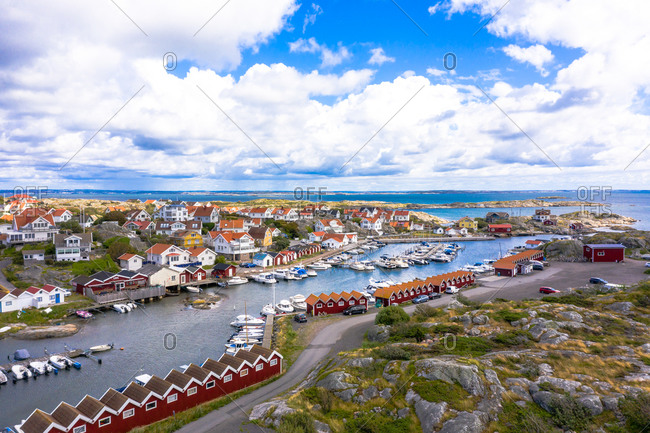 Panoramic aerial view of the harbor area with typical red boat houses and anchored boats, Gothenburg Archipelago, Sweden.
