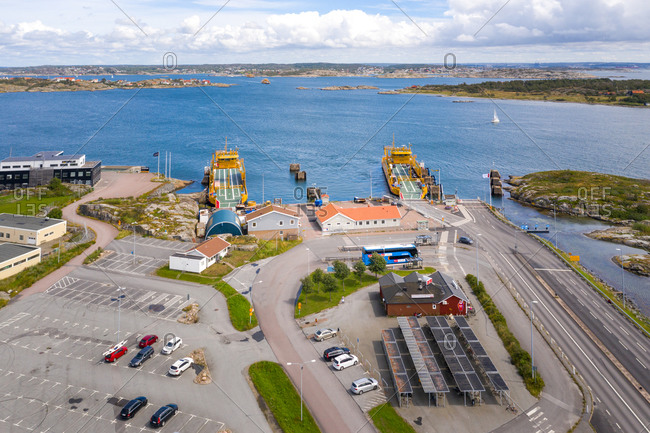 July 25, 2020: Aerial view of the ferry terminal with two yellow car ferries, parking area, Gothenburg Archipelago, Sweden.