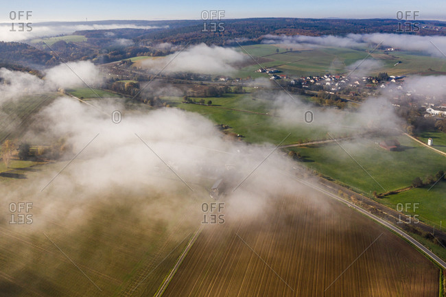 Panoramic aerial view of a rural autumn landscape with dissolving fog, Hessia, Germany.