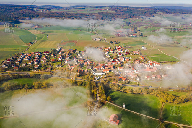 Panoramic aerial view of a rural autumn landscape with a fog layer covering a village, Hessia, Germany.
