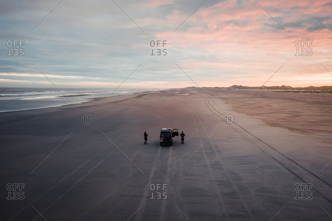 Aerial view of two people and a camper van on a wide stretched beach on the island Terschelling, Friesland, The Netherlands.