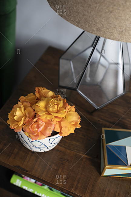 Overhead view of a wooden table with flowers and lamp