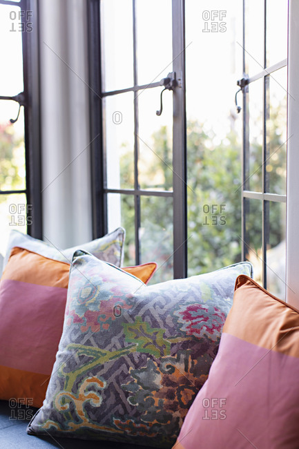 Colorful pillows on seat by open window